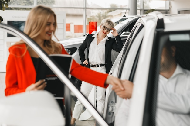 Auto dealer and buyer shake hands making a deal. . Premium Photo