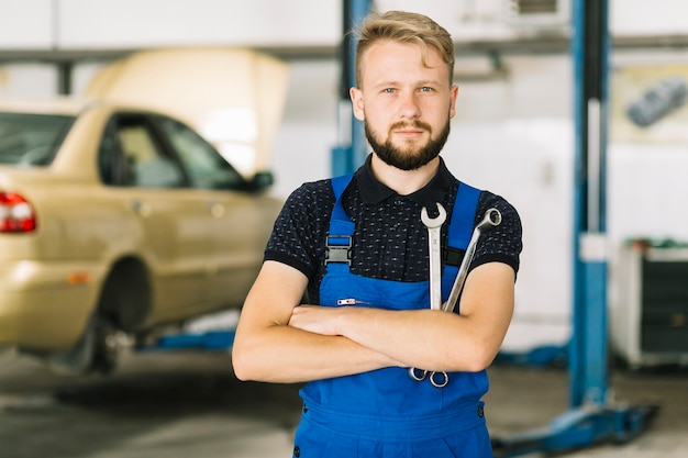 Auto mechanic crossing hands with spanners Free Photo
