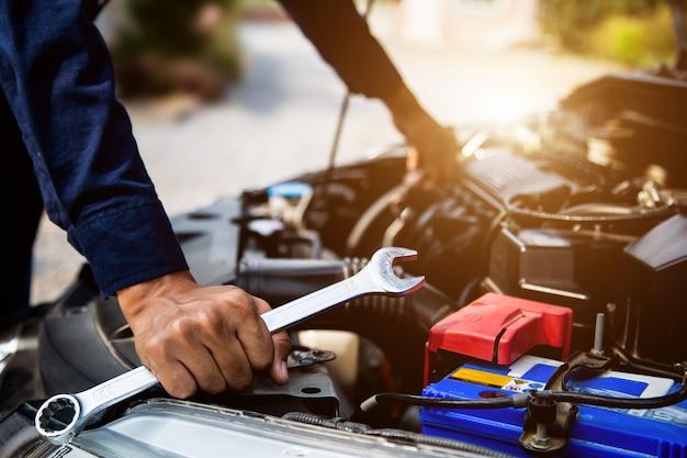 Автомеханик руки, используя гаечный ключ для ремонта и проверки системы двигателя автомобиля. Premium Фотографии