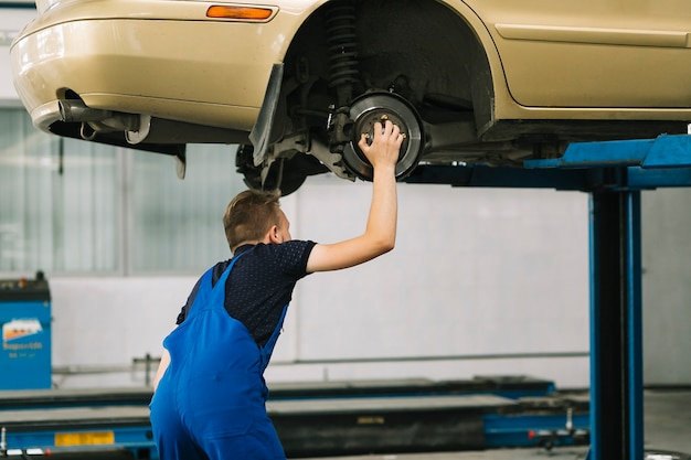 Auto mechanic holding hob on car Free Photo