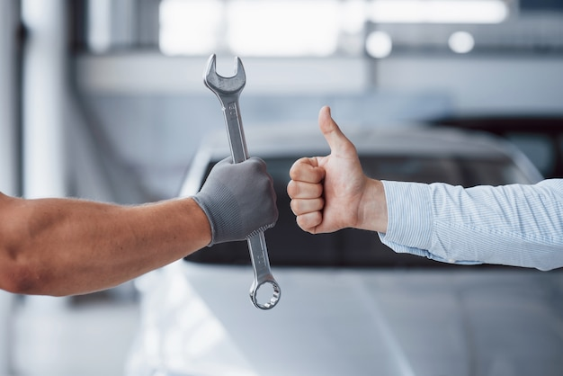 The auto mechanic holds the key in the client's hand and lifts his thumb up. well done work Premium Photo