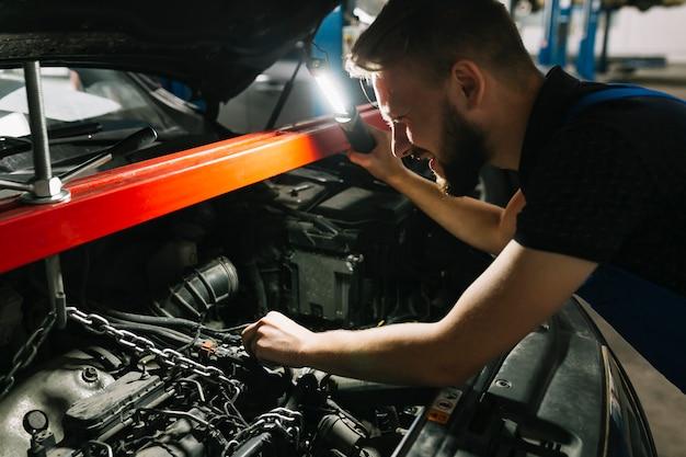 Auto mechanic looking car's engine Free Photo
