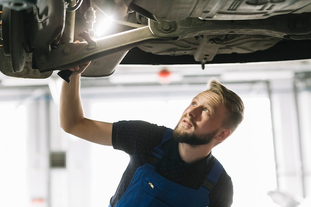 Auto mechanic looking car's nave Free Photo