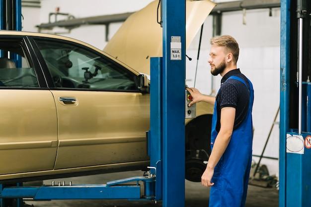 Auto mechanic pressing push button Free Photo