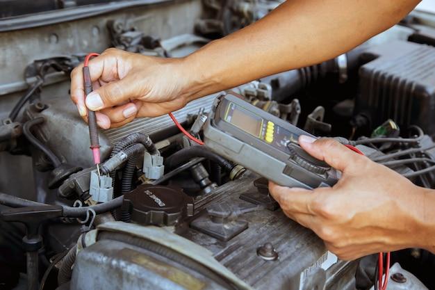 Автомеханик, использующий измерительное оборудование для проверки электрических автомобилей. Premium Фотографии