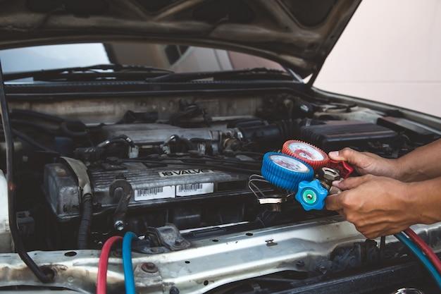 Автомеханик, использующий измерительное оборудование для проверки заправки автомобильных кондиционеров. Premium Фотографии