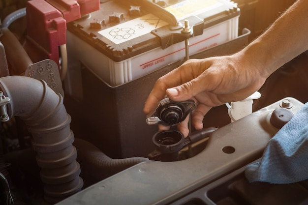 Auto mechanic working check system water and battery fill an old car engine at service station,change and repair before drive Premium Photo