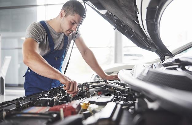 Meccanico auto che lavora in garage. servizio di riparazione. Foto Gratuite