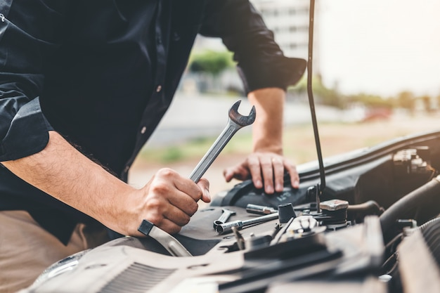 Auto mechanic working in garage technician hands of car mechanic working in auto repair Premium Photo
