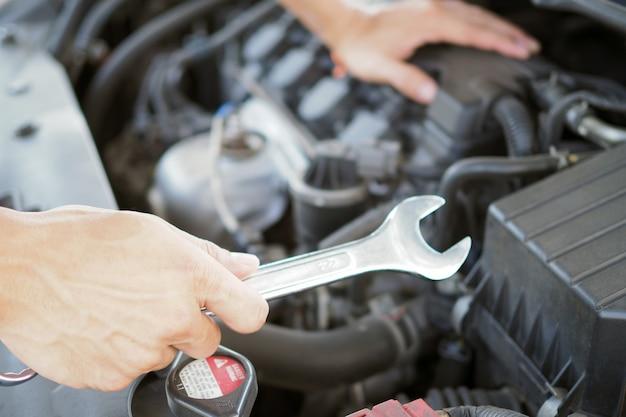 Auto repairman is working to fix the engine. Premium Photo