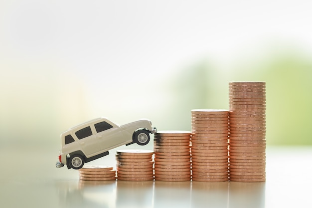 Automobile business finance concept. close up of white miniature car toy on stack of coins with copy space. Premium Photo