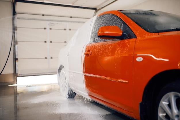 Автомобиль наполовину в пене, автомойка Premium Фотографии