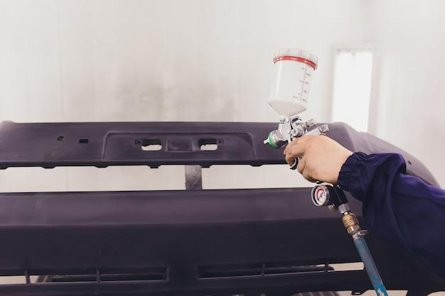 自動車用塗料。自動車修理工場で車を塗装するメカニック。 Premium写真