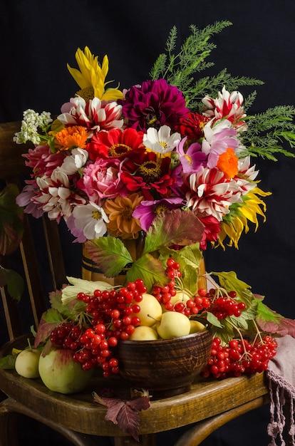黒い表面に庭の花、赤い果実、リンゴ、紅葉のカラフルな美しい花束のある秋の雰囲気のある静物。 Premium写真