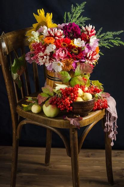 Осенний атмосферный натюрморт с красочным красивым букетом садовых цветов, красных ягод, яблок, осенних листьев на черной поверхности. Premium Фотографии
