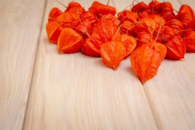 Осенний фон. ярко-оранжевые ягоды физалиса на ярком древесном фоне. Premium Фотографии