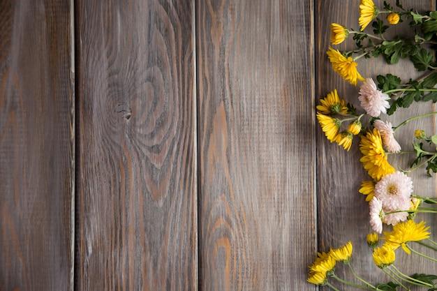 Осенний фон. цветы на фоне коричневого дерева. Premium Фотографии