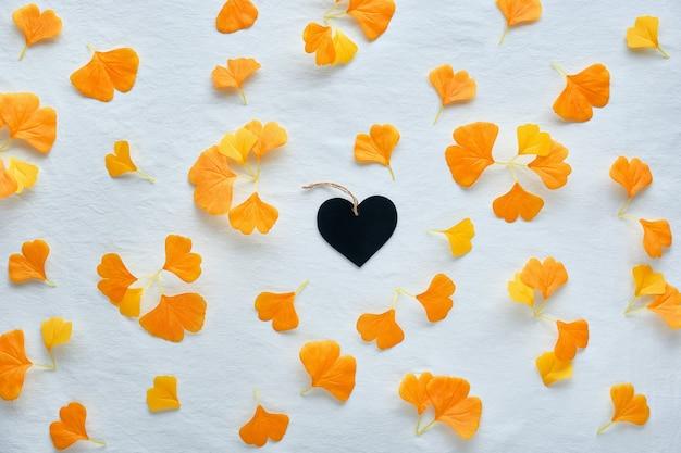 오렌지와 브라운 이을 배경. 실크 오렌지 은행 나무는 흰색 섬유 배경에 나뭇잎. 중간에 검은 나무 심장. 프리미엄 사진