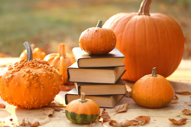 Autumn books. halloween books. stack of books and  pumpkins  on a blurry background in  sunshine. Premium Photo