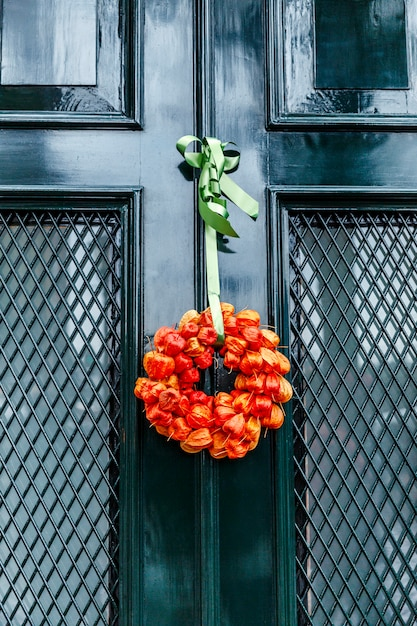 Autumn bouquet of dried orange flowers on a green entrance door to the house. vertical. Premium Photo