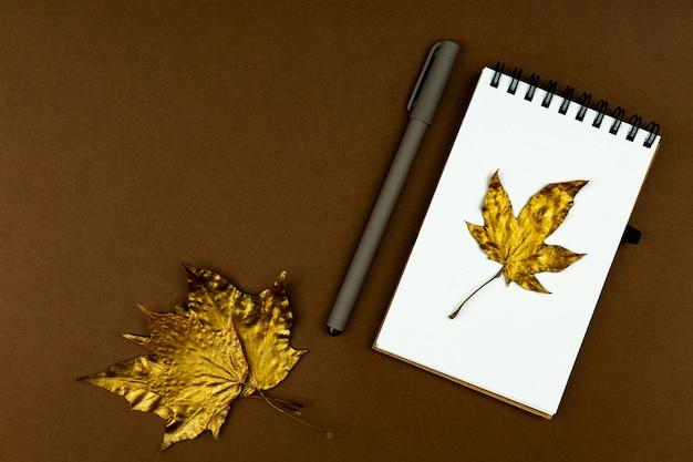 秋のビジネスコンセプト-茶色の平らな場所に金色のカエデの葉とペンが付いた空白のリング製本ノート Premium写真