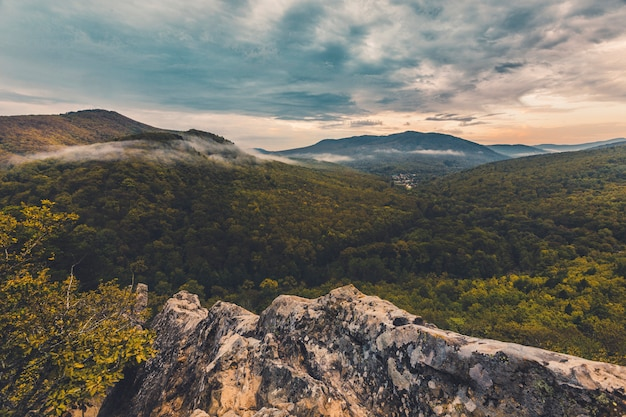 Autumn cold morning dawn in the mountains above the valley floating clouds Premium Photo
