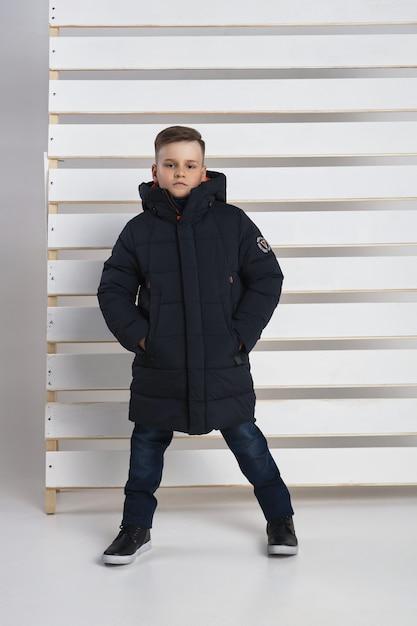 Осенняя коллекция одежды для детей и подростков. куртки и пальто на осеннюю холодную погоду. дети позируют на белом фоне. Premium Фотографии
