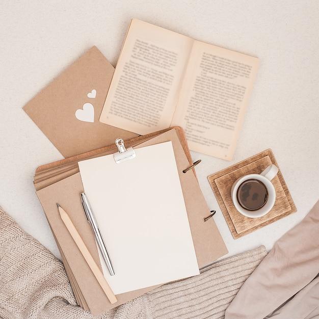秋の組成。コーヒー、本、毛布、ノート、女性のファッションセーターのカップ。 Premium写真