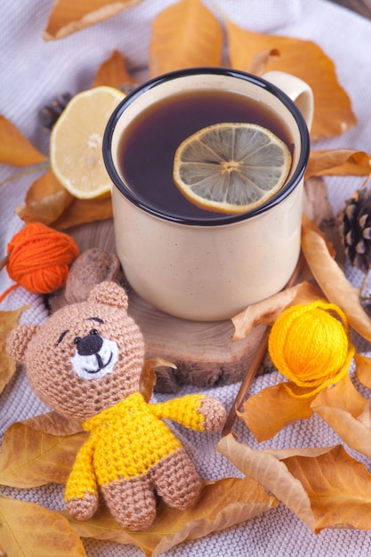 Autumn composition, cup of tea with lemon. sunday relaxing and still life concept. knitted toy, teddy, amigurumi. handmade. diy Premium Photo