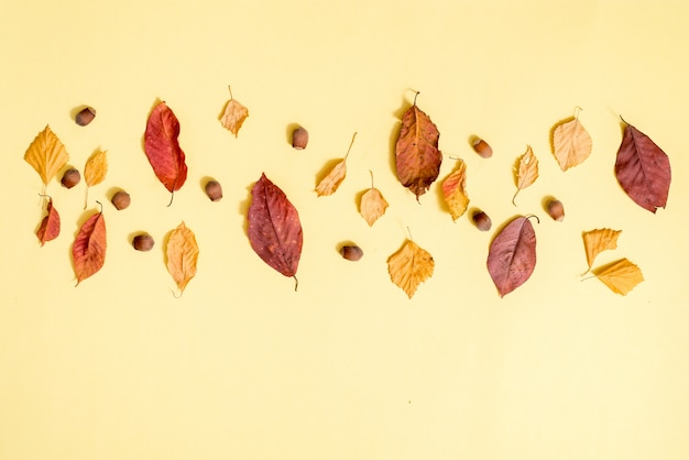 Autumn composition, fall leaves, hot steaming cup of tea and a warm scarf on wooden table background. Premium Photo