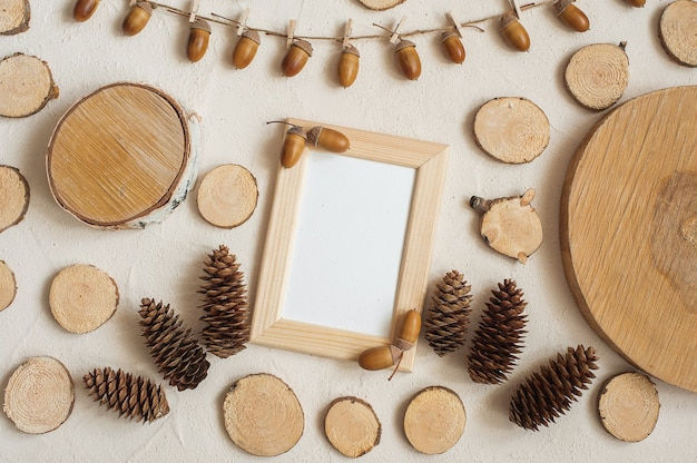 Autumn composition, frame made of pine cones, acorns and small wooden stumps. Premium Photo