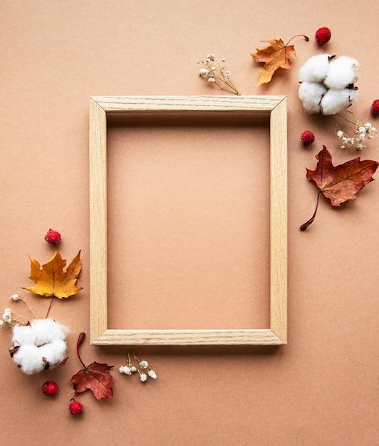 秋の構成。フォトフレーム、花、茶色の背景の葉。秋、秋、感謝祭のコンセプト。フラットレイ、上面図、コピースペース Premium写真