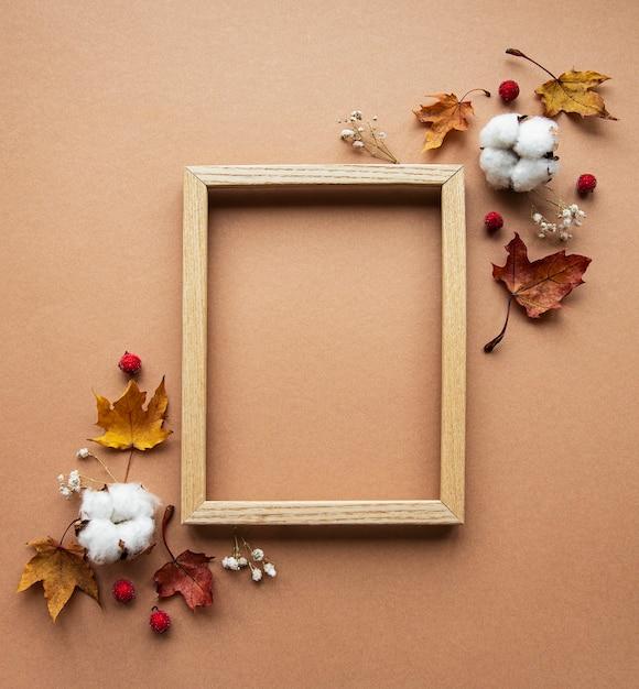 秋の構成。フォトフレーム、花、茶色の背景の葉。秋、秋、感謝祭のコンセプト。 Premium写真