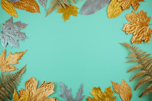 Autumn composition with golden leaves frame on blue mint background Premium Photo