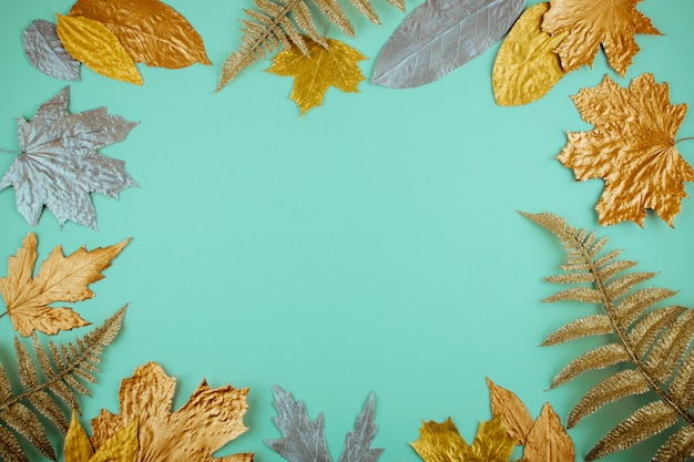 Autumn composition with golden leaves frame on mint Premium Photo