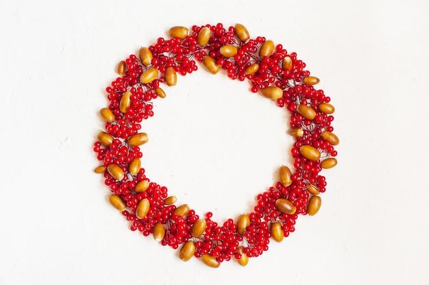 Autumn composition with red berry and  acorns. wreath made of viburnum berries. Premium Photo