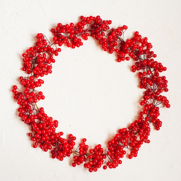 Autumn composition with red berry. wreath made of viburnum berries Premium Photo