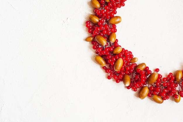 Autumn composition with red berry. wreath made of viburnum berries Premium Photo