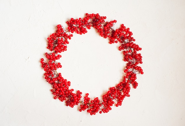 Autumn composition with red berry. wreath made of viburnum berries. Premium Photo