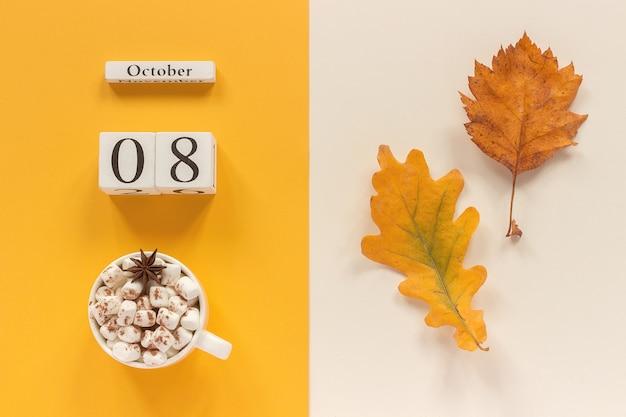 Осенняя композиция. деревянный календарь 8 октября, чашка какао с зефиром и желтыми осенними листьями на желтом бежевом Premium Фотографии