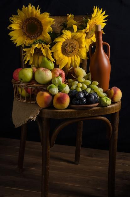 秋の宝庫。暗いスタイルで黒い表面に果物、ブドウ、ワインのヒマワリのある静物。感謝祭と収穫。 Premium写真