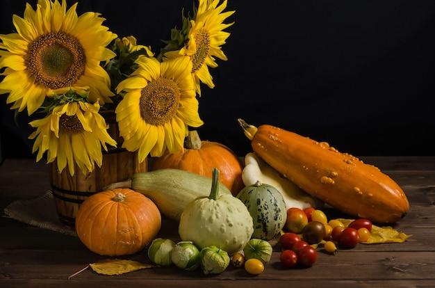 秋の宝庫。コピースペースと黒い表面に野菜からのヒマワリのある静物。感謝祭と収穫。 Premium写真