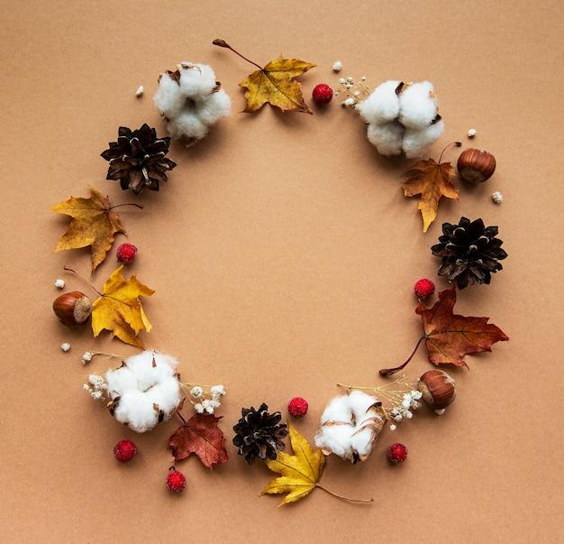 茶色の背景に円の形をした綿の花と乾燥したカエデの葉の秋の装飾 Premium写真
