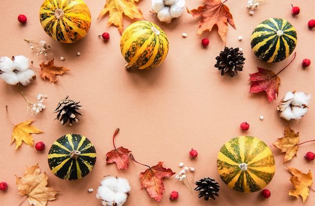 カボチャと茶色の乾燥したカエデの葉で秋の装飾 Premium写真