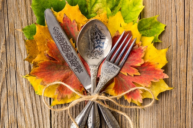 Autumn dinner place setting for thanksgiving holiday with colorful maple leaves on rustic wooden boards Premium Photo