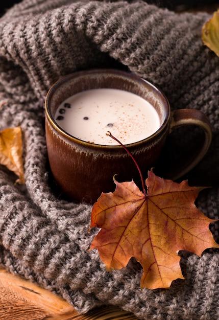 Осенний напиток с молоком рядом с серым шарфом Premium Фотографии