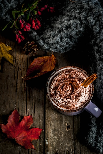 Autumn drinks, hot chocolate or cocoa with whipped cream and spices (cinnamon, anise), on the old rustic wooden table, with a warm cozy blanket, hay berry and leaves copyspace top view Premium Photo