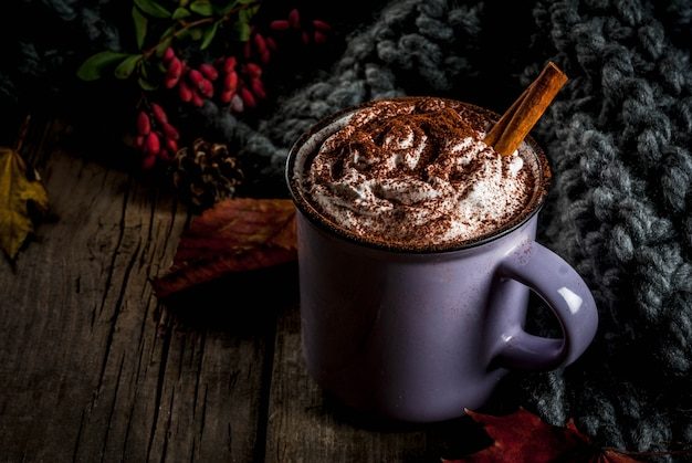 Autumn drinks, hot chocolate or cocoa with whipped cream and spices (cinnamon, anise), on the old rustic wooden table, with a warm cozy blanket, hay berry and leaves copyspace Premium Photo