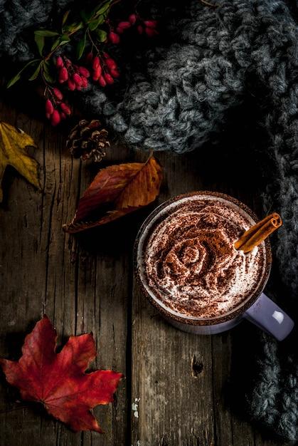 Осенние напитки, горячий шоколад или какао со взбитыми сливками и специями (корица, анис), на старом деревенском деревянном столе, с теплым уютным одеялом, сенной ягодой и листьями copyspace вид сверху Premium Фотографии