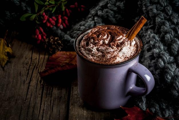 Осенние напитки, горячий шоколад или какао со взбитыми сливками и специями (корица, анис), на старом деревенском деревянном столе, с теплым уютным одеялом, сенной ягодой и листьями copyspace Premium Фотографии
